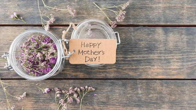 Inscription heureuse fête des mères avec des fleurs en canette