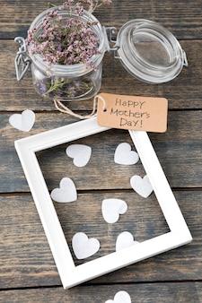 Inscription heureuse fête des mères avec des fleurs, des coeurs et un cadre