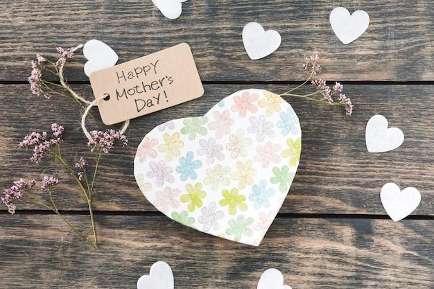 Inscription heureuse fête des mères avec des fleurs un coeurs de papier