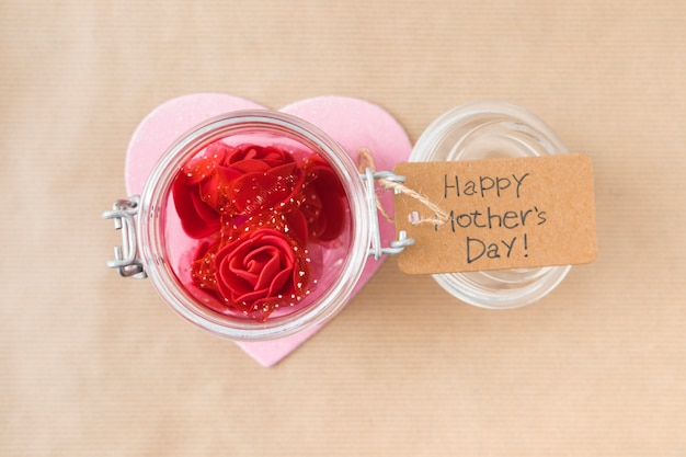 Inscription heureuse fête des mères avec des fleurs roses en boîte