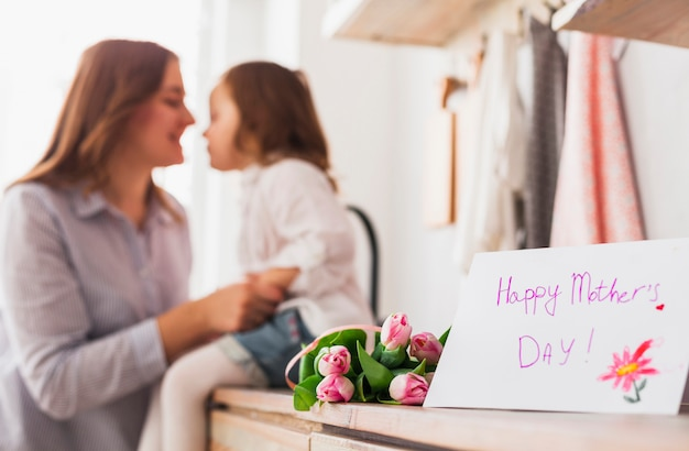 Inscription heureuse fête des mères près de mère et fille