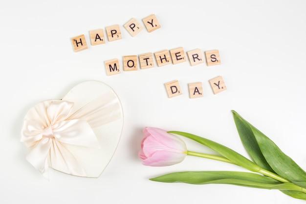 Inscription heureuse fête des mères avec tulipe et cadeau