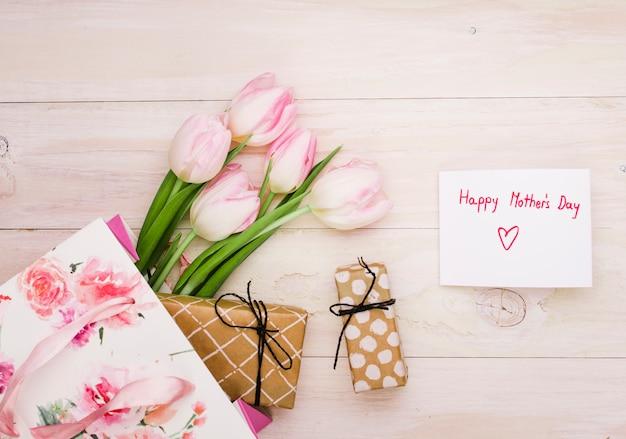 Inscription heureuse fête des mères avec des tulipes et des cadeaux