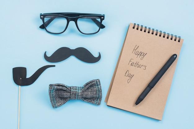 Inscription heureuse fête des pères dans le bloc-notes avec lunettes et moustache