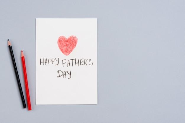 Inscription heureuse fête des pères sur papier avec des crayons