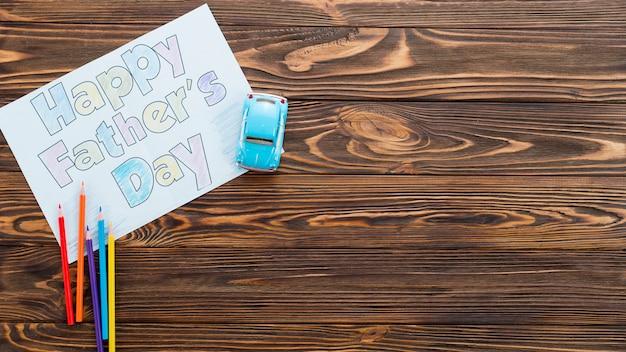 Inscription heureuse fête des pères avec voiture de jouet sur la table