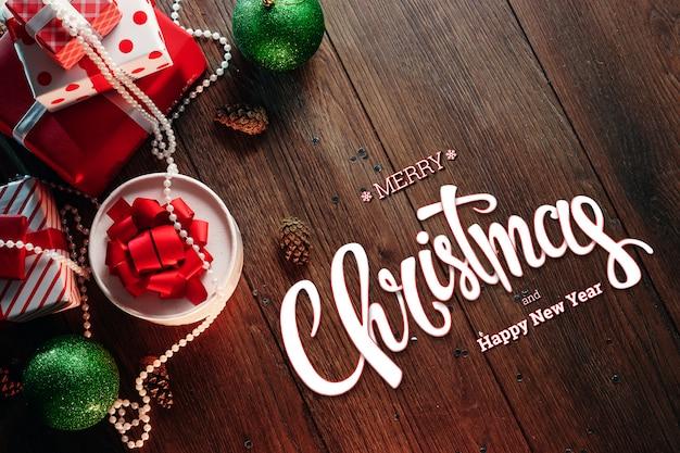 L'inscription de joyeux noël, des décorations et des cadeaux sur une table en bois marron. carte de noël, vacances. technique mixte.