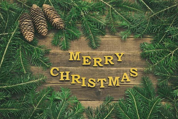 Inscription joyeux noël sur un fond en bois. cadre fait de branches de sapin et de cônes. concept de vacances