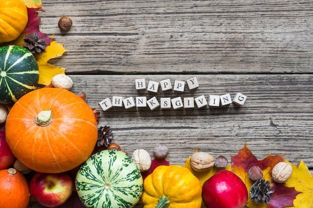 Inscription joyeux thanksgiving avec fruits et légumes d'automne avec des feuilles d'érable