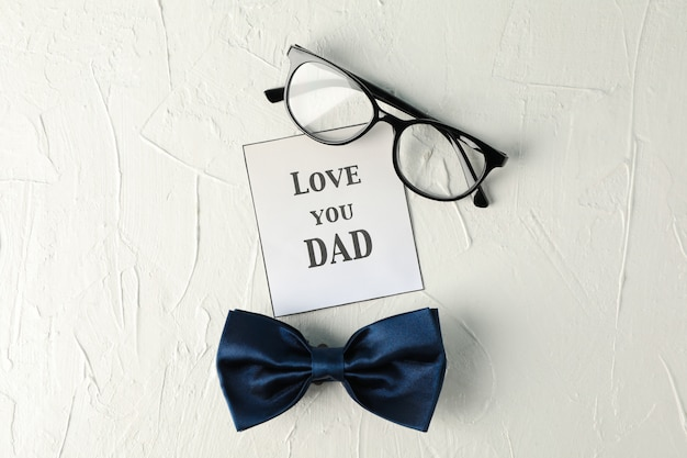 Inscription love you dad, noeud papillon bleu et lunettes sur fond blanc, espace pour le texte et vue de dessus