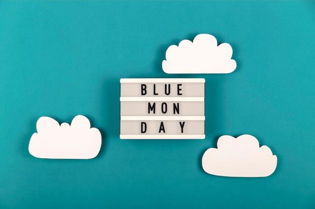 Inscription lundi bleu parmi les nuages de papier sur fond bleu. concept d'humeur dépressive
