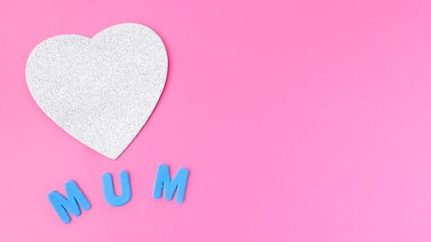 Inscription de maman avec coeur de papier sur la table