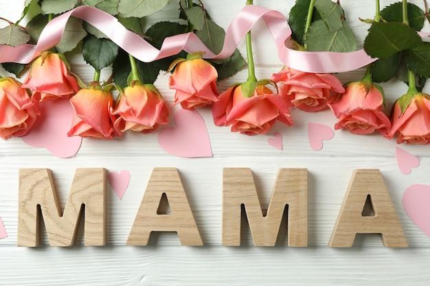 Inscription maman avec roses roses, ruban et petits coeurs sur table en bois, vue de dessus