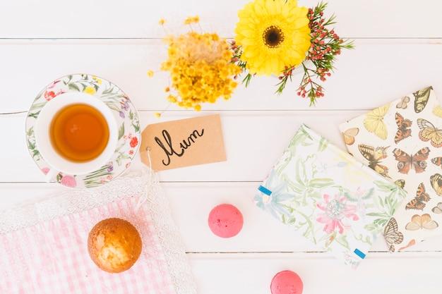 Inscription de maman avec une tasse de thé et des fleurs