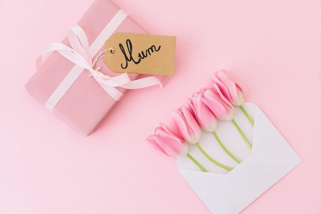 Inscription de maman avec des tulipes dans une enveloppe et une boîte cadeau