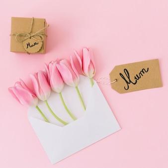 Inscription de maman avec des tulipes dans une enveloppe et un cadeau