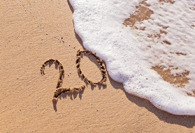 Inscription manuscrite 20 sur le sable avec vague mousseuse
