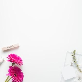 Inscription de mars avec des fleurs de gerbera et du papier