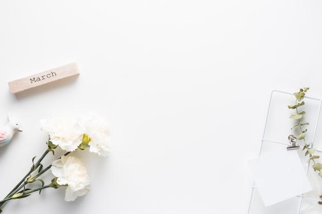 Inscription de mars avec des fleurs d'oeillets et du papier