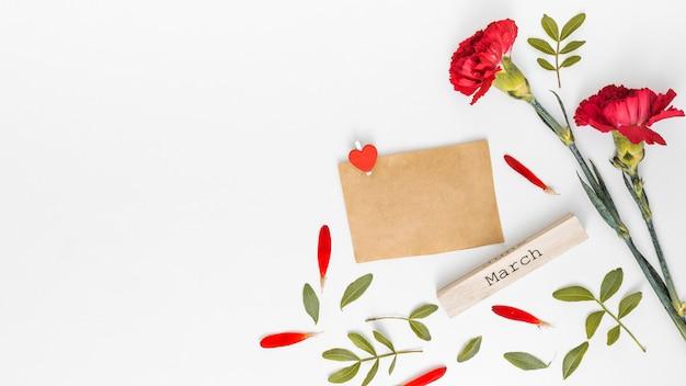 Inscription de mars avec des fleurs d'oeillets rouges et du papier