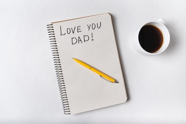 Inscription mignonne dans le cahier je t'aime papa. café, bloc-notes et stylo. vue de dessus