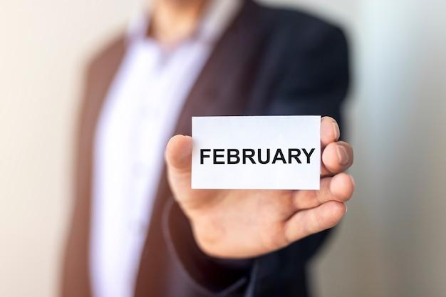 Inscription de mot février dans la main de l'homme d'affaires se bouchent.