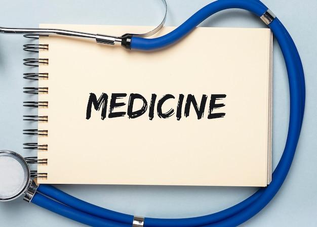 Inscription de mot médecine sur le bloc-notes avec stéthoscope.