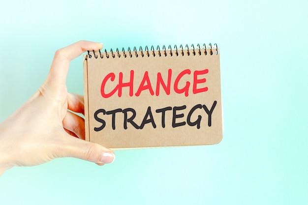 Inscription de mot de stratégie de changement sur une feuille de papier de carte dans les mains d'une femme d'affaires. lettres noires sur papier blanc