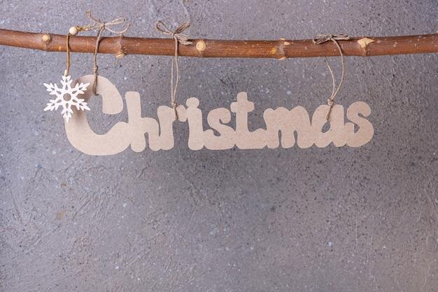 L'inscription noël est découpée dans du carton et accrochée à une branche pour le texte