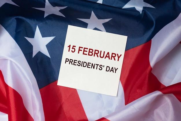 Inscription sur papier avec fond de drapeau américain. journée du président aux états-unis.