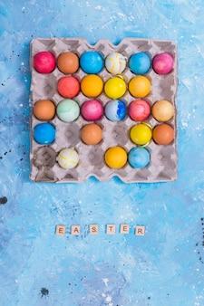 Inscription de pâques avec des oeufs colorés dans un rack