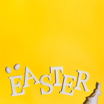Inscription de pâques avec des oeufs et un lapin sur la table