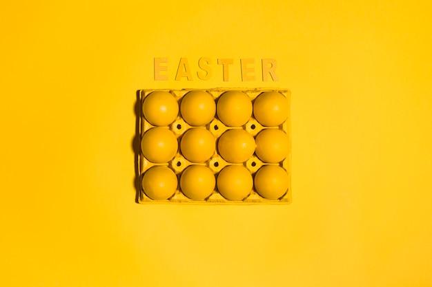 Inscription de pâques avec des oeufs en rack sur une table jaune
