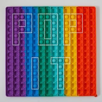Inscription pop it sur fond coloré pop it est un élément de conception de symbole de lettre de jouets en silicone