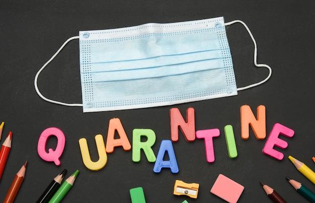 Inscription en quarantaine à partir de lettres en plastique multicolores et de fournitures scolaires sur tableau noir, concept de fermeture des écoles pendant une pandémie