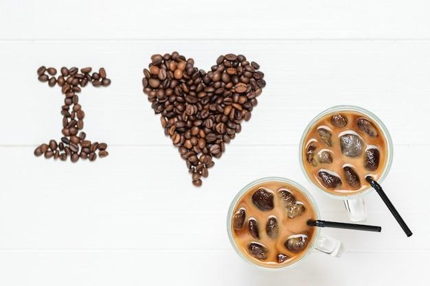 L'inscription que j'aime et deux verres de café froid sur une table en bois blanche. boisson rafraîchissante et revigorante de grains de café et de lait. la vue du haut. mise à plat.