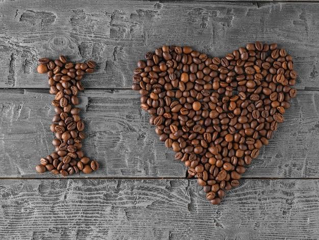 L'inscription que j'aime doublée de grains de café sur une table sombre.