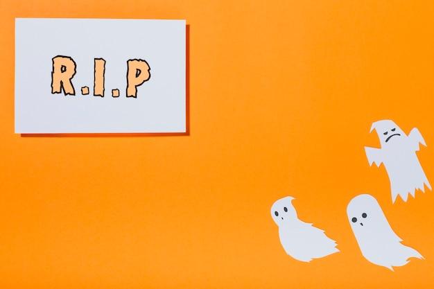 Inscription rip sur feuille de papier et petits fantômes blancs