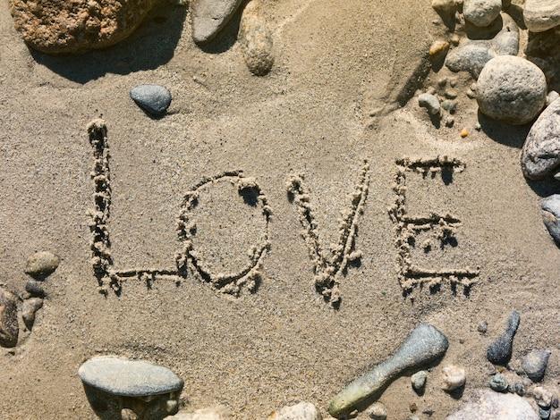 Inscription sur le sable de la rivière amour entouré de pierres colorées concept romantique