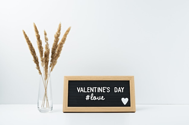 L'inscription saint valentin dans un cadre de fleurs sèches dans un vase transparent sur blanc.