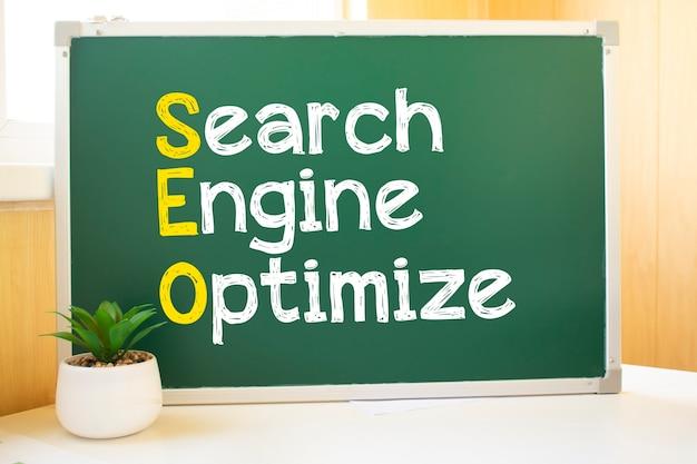 Inscription seo à la craie sur la commission scolaire, optimisation des moteurs de recherche et sites web. bureau, boules de papier balayées, clavier d'ordinateur