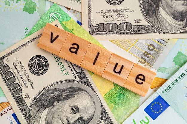 Inscription de la valeur sur des cubes en bois sur la texture des dollars américains et des billets en euros