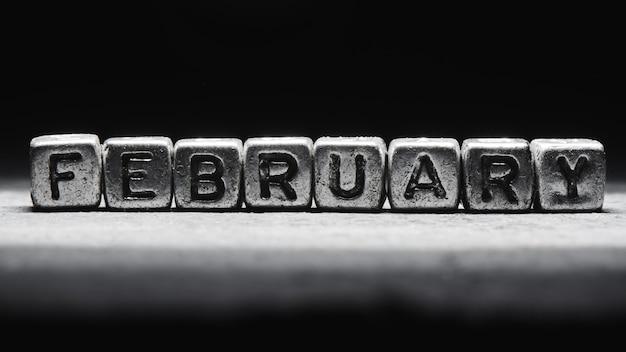 Inscription volumétrique de cubes en métal argenté de février sur fond noir foncé. calendrier des délais, planification personnelle et gestion du temps