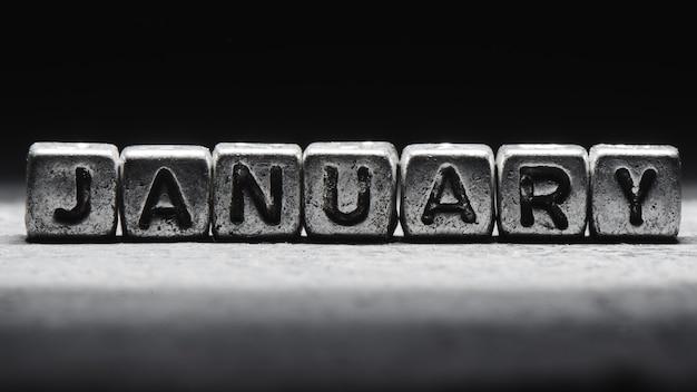 Inscription volumétrique de cubes en métal argenté de janvier sur fond noir foncé. calendrier des délais, planification personnelle et gestion du temps