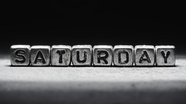 Inscription volumétrique samedi cubes en métal argenté sur fond noir foncé. calendrier des délais, planification personnelle et gestion du temps, sept jours sur sept