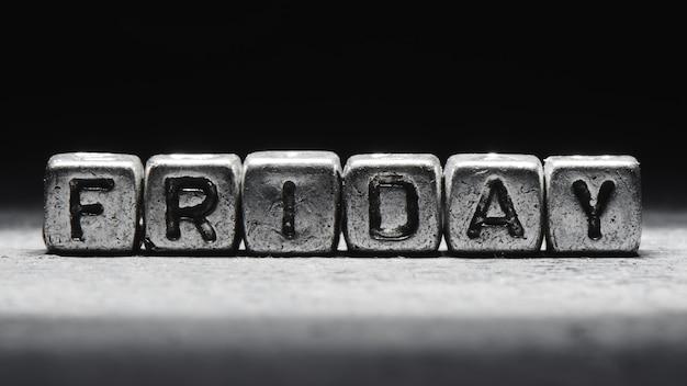 Inscription volumétrique vendredi cubes en métal argenté sur fond noir foncé. calendrier des délais, planification personnelle et gestion du temps, sept jours sur sept