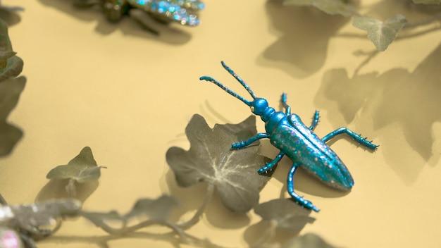Insecte en plastique parmi les feuilles vertes