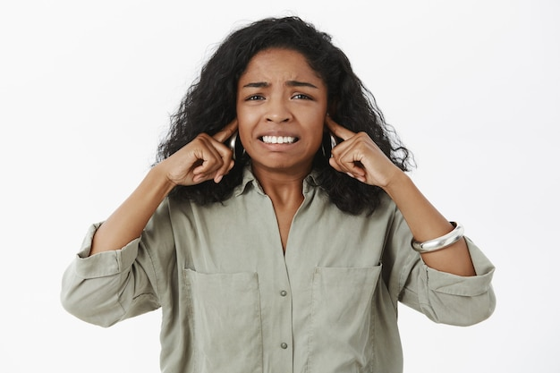 Insécurité irrité, mécontent femme afro-américaine en chemise à la mode serrant les dents fermant les oreilles avec l'index