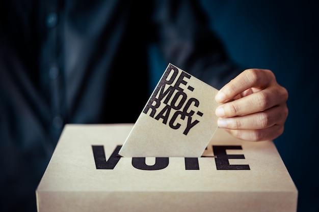 Insert de papier brun dans la boîte de vote, concept de démocratie, ton rétro