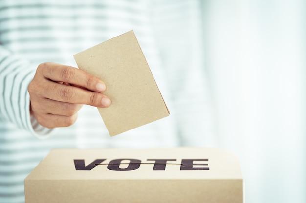 Insert de papier brun dans la boîte de vote